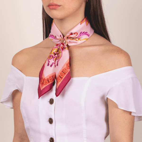 medium sized pink and wine colored El Canto kerchief worn as women's neck scarf.