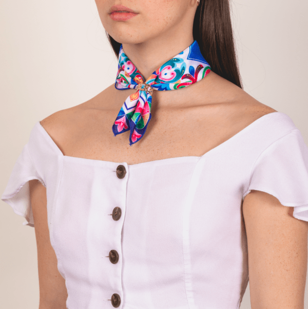 brightly colored El Canto kerchief worn as neck wrap.