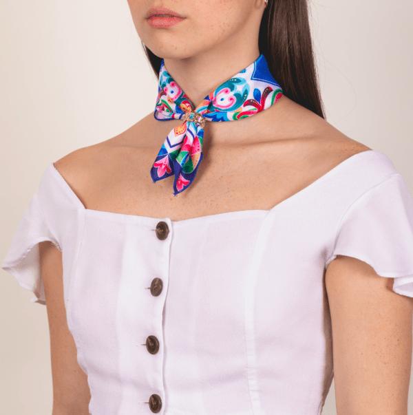 brightly colored El Canto kerchief worn as neck wrap.