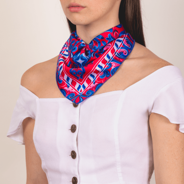 woman wearing blue, red and white El Canto scarf handkerchief on décolletage area.