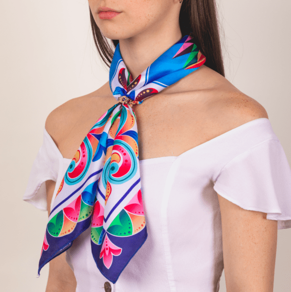 bright rainbow colored large El Canto kerchief worn on woman as long neck scarf.