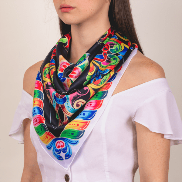 large black, white and bold colored El Canto kerchief worn as large and long décolletage accessory scarf.