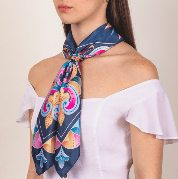 large pastel and peacock blue colored El Canto kerchief scarf worn as long neck accessory wrap.