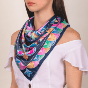 large sized pastel and peacock blue El Canto kerchief worn as long décolletage scarf.