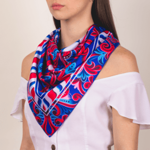 blue, red and white El Canto Costa Rican handkerchief worn as large décolletage accessory piece.