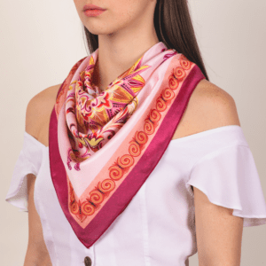 pink terracotta colored large sized El Canto kerchief worn as large décolletage accessory.