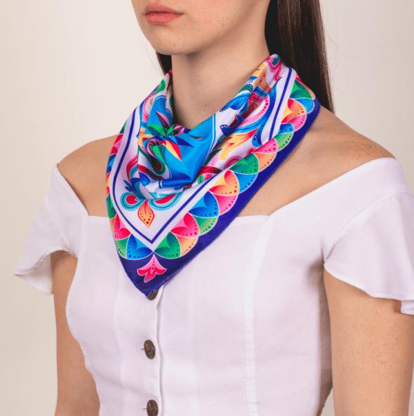 bright rainbow colored medium sized El Cando kerchief worn as décolletage accessory scarf.