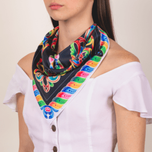 medium sized bold rainbow and black colored El Canto kerchief worn as décolletage accessory.