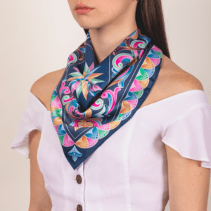 medium sized pastel El Canto kerchief worn as décolletage scarf.