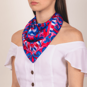 red, white, pink and blue medium sized El Canto kerchief worn as décolletage scarf.