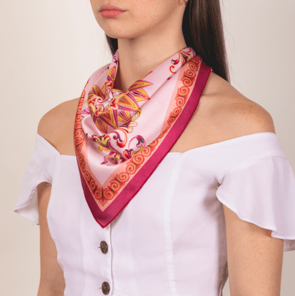 pink and wine colored medium sized kerchief by El Canto worn as décolletage accessory.