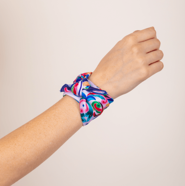 bright colored El Canto kerchief wrapped and knotted around wrist.