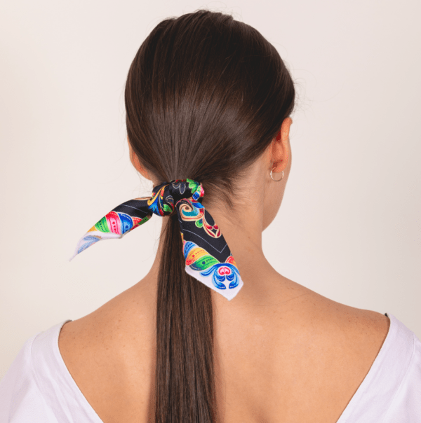 bold and black colored El Canto kerchief wrapped and tied around hair in ponytail .