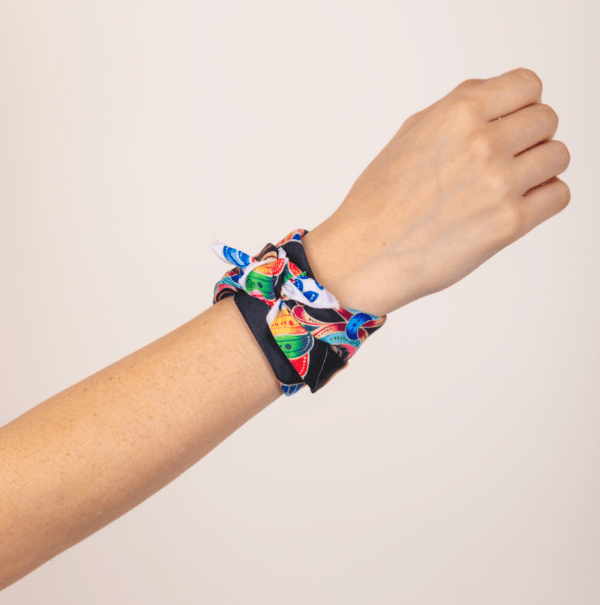 bold and black colored kerchief by El Canto worn as knotted wrist wrap.