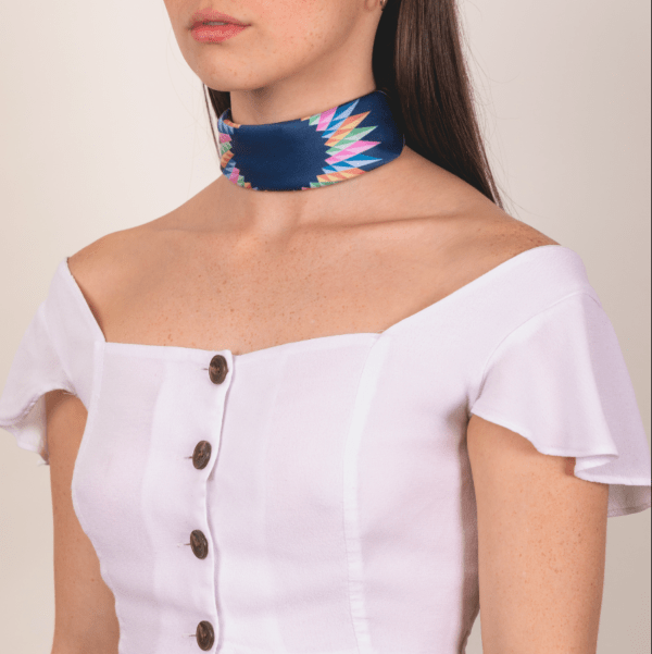 pastel and peacock blue El Canto kerchief worn as woman's wide choker neck piece.