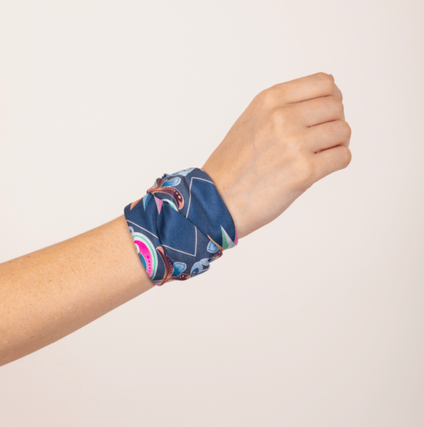 pastel and peacock blue kerchief wrapped as woman's wrist accessory .