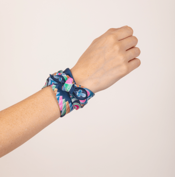 pastel El Canto kerchief worn as knotted wrist wrap.