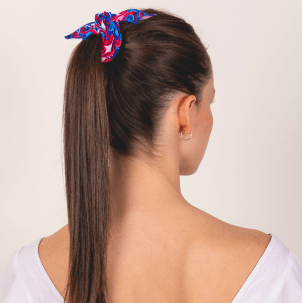Woman wearing blue, red and white El Canto handkerchief scarf ponytail hair accessory wrap.