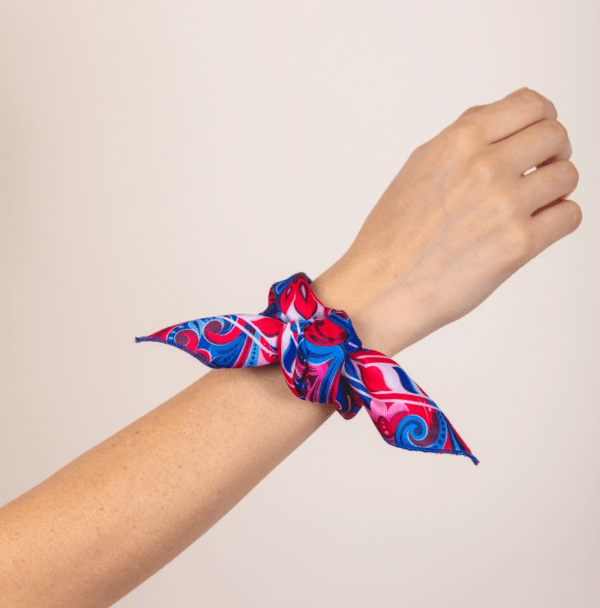 blue, red and white El Canto Costa Rican handkerchief tied in artful knot around woman's wrist.