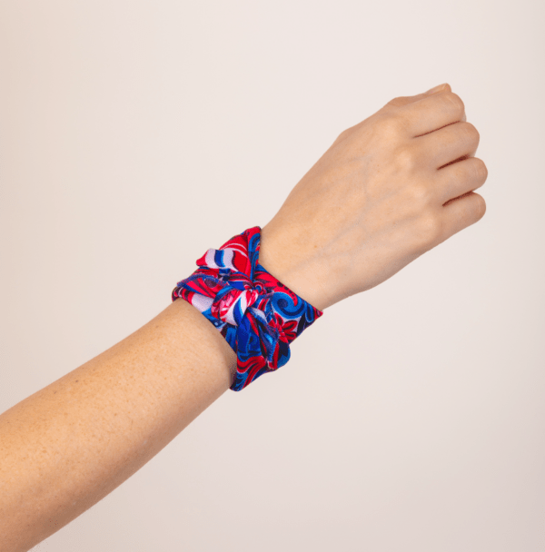 blue and red El Canto handkerchief scarf wrapped around woman's wrist.