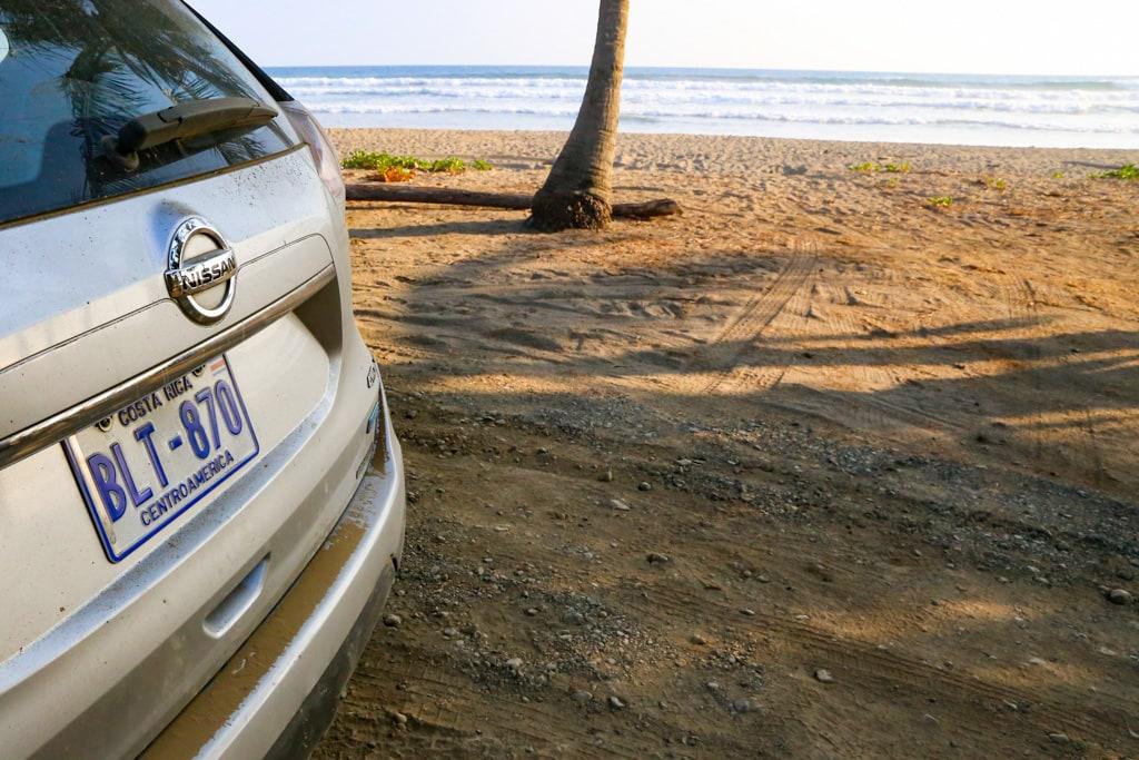 costa rician beach next to rental car .