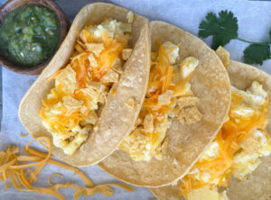three homemade migas torchy's tacos with side of green salsa