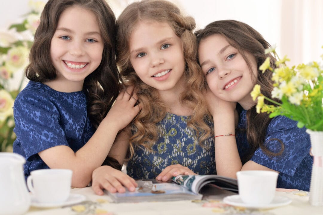 three young girls smiling and reading magazine