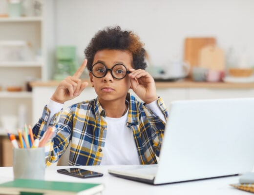boy of color with glasses laptop learning