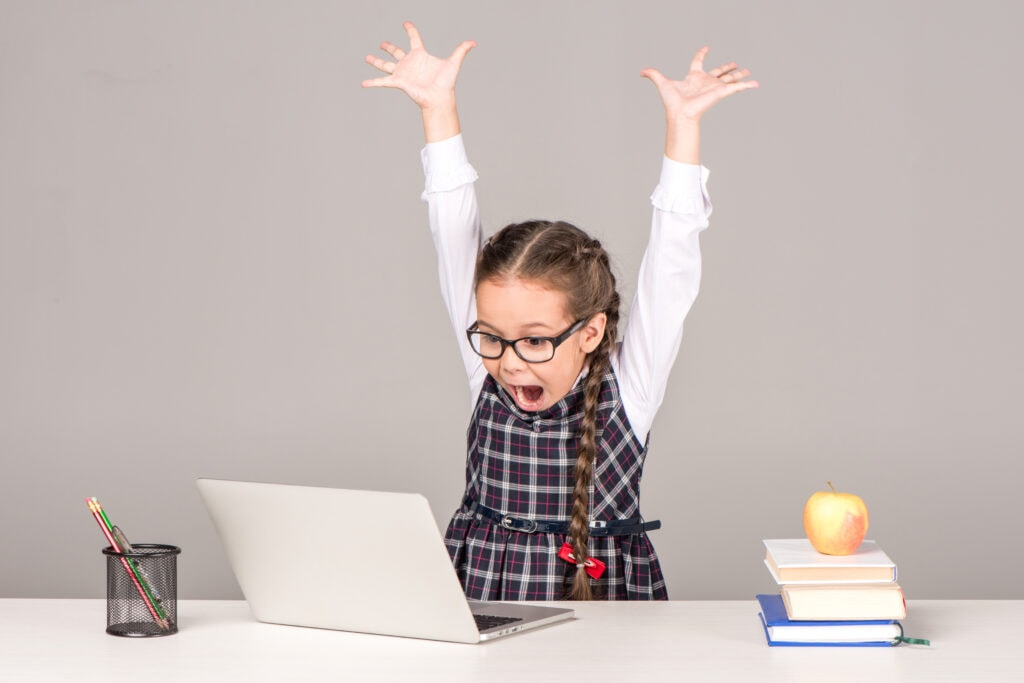 little girl with glasses with her hands up