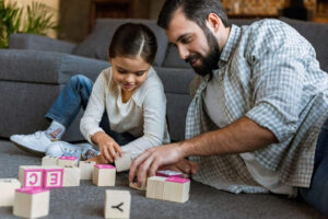 man and child playing blocks on the floor