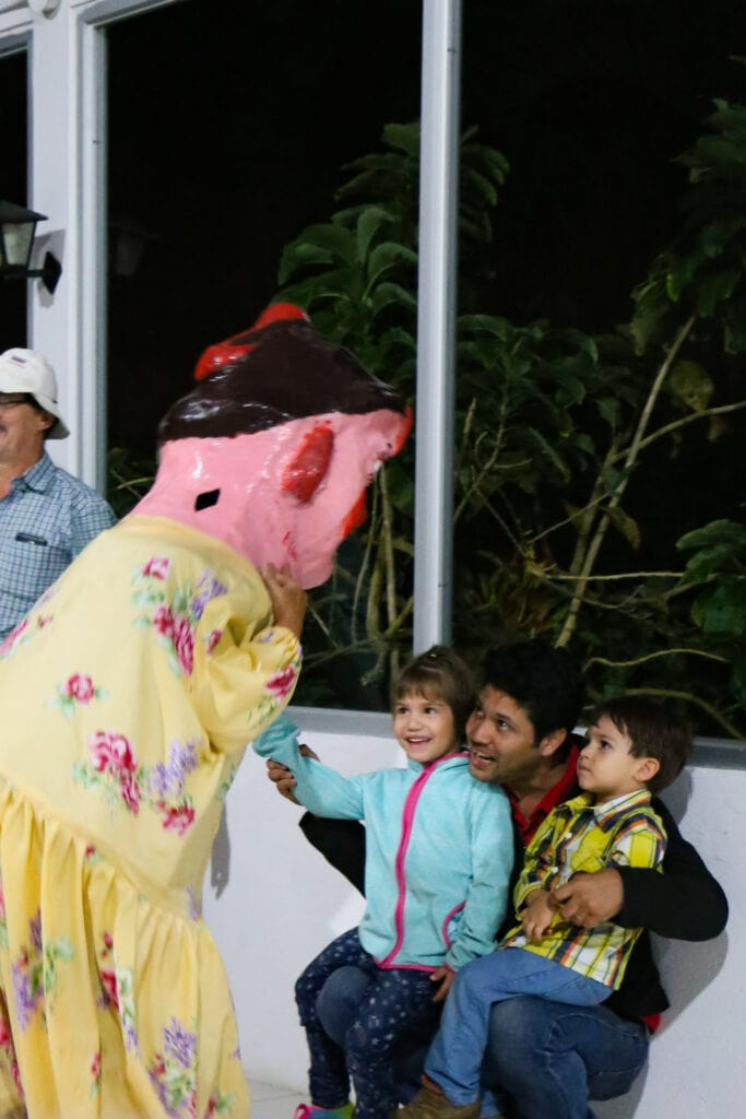 costa rican enmasacarada greets young children with father